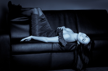 lying on couch: sensual woman lying on a leather sofa, selenium tone Stock Photo
