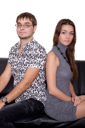 funny nerd guy and glamorous girl sitting on the sofa isolated on white photo