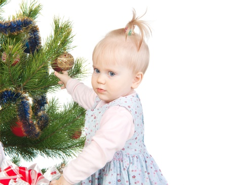 cute baby girl standing near the Christmas tree isolated on white photo
