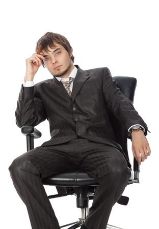 young attractive man with a cigar pensively sitting in an armchair photo