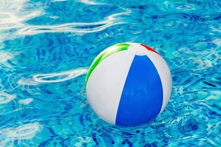 Multi colored Beach ball in swimming pool Stock Photo