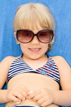little girl with sunglasses in a deck chair photo