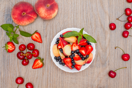 Delicious fruit salad on a wooden background. Top view.