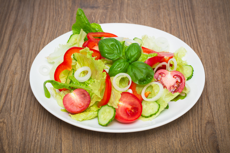 fresh vegetarian salad in a white plate on the wooden table