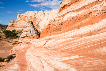cone shaped: Orange and white sandstone layers interact in waves and stripes in the forground and a small cone shaped tower rises from the formation on the left. In the background is a large cliff of similar colors.