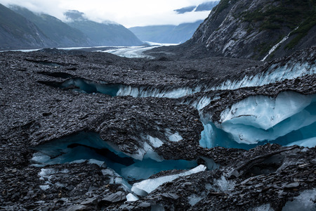A series of crevasses split Valdez glacier into many strange shapes and formations in the foreground. In the background, the glacier is seen for miles up the valley it is slowly  carving as it flows toward its terminus at Valdez Lake. Black moraine (unso