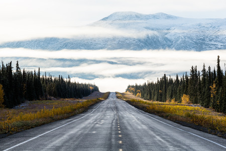 yukon territory: Early morning light illuminates this northern scene in the Yukon Territory of Canada. A two lane road disappears into thick fog, while above, a snowy peak sticks out above the cloud layers