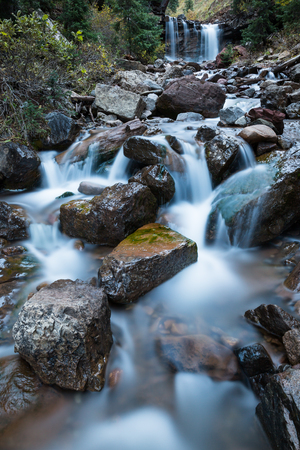 A small river or creek runs through a rocky area in Colorado. In the background a waterfall pours over a cliff, and a small cascaderuns through the rocky creek bed in the forground. A long exposure smooths out all the flowing water into soft white ribbons Stock Photo