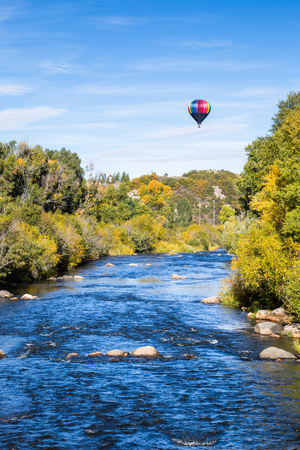 Trees are starting to turn yellow in autumn as a hot air balloon floats above a calm blue river near Steamboat Springs, Colorado.
