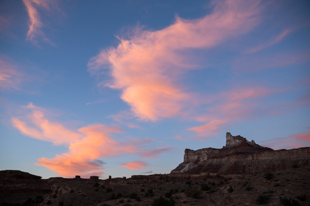 Sunset in the San Rafael Swell of Southern Utah. Clouds glow pink after shadows cover the landscape just after sunset. Uranium Mining brought hundreds of people to this landscape in the 1900s, and now it is mostly left alone as wilderness