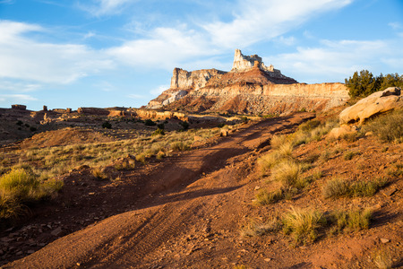 San Rafael Swell: A washed out dirt road leads to the base of Temple Mountain. in the early 1900s hundreds of mining claims dotted the area around Temple Mountain in the San Rafael Swell of Southern Utah. Stock Photo