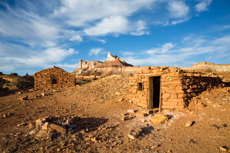 San Rafael Swell: A Camp left over from the 1900s Uranium mine boom in Southern Utah. Two buildings along with a more recent fire ring are left below the steep cliffs of Temple Mountain. It is thought that Marie Curie visited the area and slept in the larger building on t Stock Photo