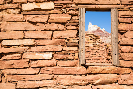San Rafael Swell: A window through an old, partially collapsed building, left over from the days of heavy uranium mining, looks on at the craggy summit of Temple Mountain in Southern Utah. It is believed that during her visit to the mines sometime in the early 1900s, Mada Stock Photo