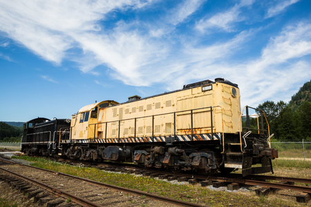 Two old enginge sit in an old railyard in Washington. The engines are still used around the yard but are worn down ad rusty.