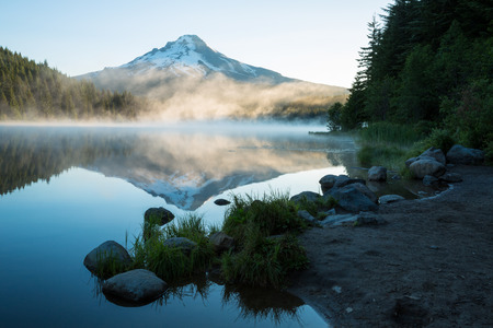 Trillium lake sits perfectly calm displaying a smooth reflection of Mt. Hood with a layer of fog around its base