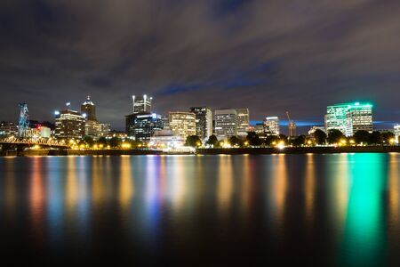 eastbank: The skyline of Portland, Oregon is reflected in the Willamette River from the Eastbank  . A seven minute exposure smooths out the ripples of the water and reflection of the city lights. Stock Photo