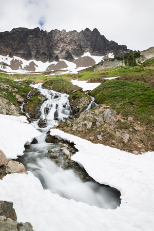 northwest: Springtime snowmelt created this stream which has cut its way under the remaining snowpack, leaving a dangerous snow bridge. above, a steep rocky face has a small patch of sunlight at the peak above a green meadow Stock Photo