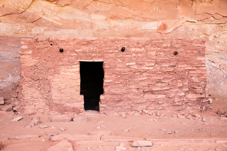 A T-shaped door into a dark dwelling built by the Pueblo people of the Southwest Desert. It is a small brick building created thousands of years ago almost perfectly preserved in the dry Utah desert. Stock Photo