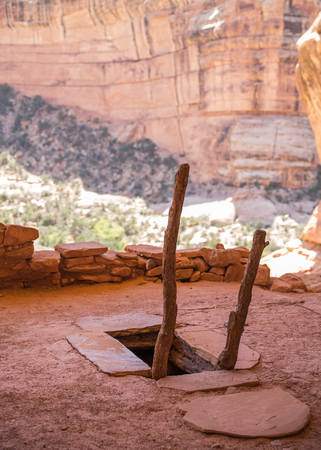 The entrance to an underground Kiva viewed from above. Dug into the ground, the Kiva is covered with logs and mud, leaving a narrow entrance and ladder to climb down inside. Kivas such as this restored one in Southern Utah were believed to be used almost