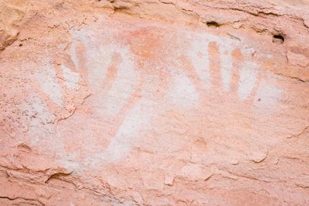 I nativi nel deserto dello Utah a volte dipingevano impronte di mani in modo positivo, con la vernice applicata sulle mani, poi premuta sul muro o con uno stile negativo. Negativi come questi sono stati fatti prendendo la sostanza della pittura in bocca o un tubo simile alla cannuccia, e premendo th Archivio Fotografico - 76128523