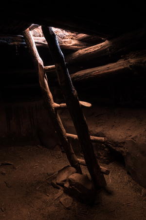 A restored ancient Kiva, dug into the ground, is lit only from the opening in the roof where a wooden ladder grants access to the interior Stock Photo