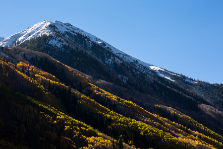 A small peak rises from the Maroon Creek Valley near Aspen, Colorado. Recent snow covers the peak as the leaves change and fall from the aspens on its slopes. The morning sun has just begun to reach through the tops of the trees and into the valley below.