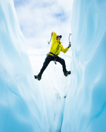 Ice climber climbing out of a crevasse on the Matanuska Glacier in Alaska. He is soloing up the span and stemming both side of the crack in the ice.
