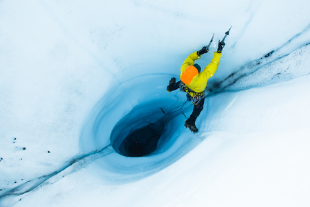 A man lead ice climbing out of a large  or hole in the ice of the Matanuska Glacier in Alaska. To start the climb, he and his belayer rappelled into the hole filled with rushing water, then pulled the rope down to begin the committing climb back to safety