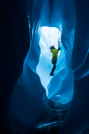 An ice climber inside of a large ice tunnel in the bottom of a . He is climbing out toward the top entrance to the hole 免版税图像