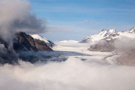 Standing at the Salmon Glacier overlook, the glacier can just be seen starting to peek out from behind the clouds below. The mountains closest to the viewpoint are still shrouded by fog but those in the distance are visible.