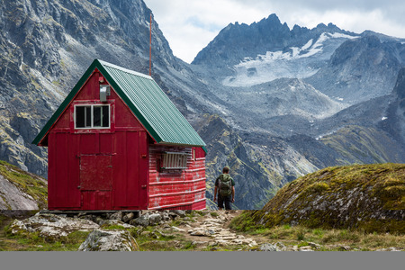 A man with a backpack out hiking walks up the trail to a red and green wilderness hut deep in the Talkeetna Mountains near Hatcher Pass, Alaska Stock Photo