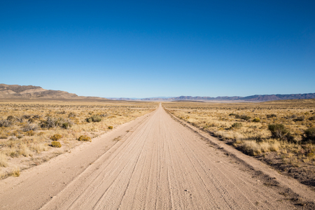 A long, straight dirt road cuts through the sage brush and empty desert of Western Utah. A low, craggy mountain can be seen on the left and a few far off peaks on the right, but otherwise a rather flat, isolated feeling.