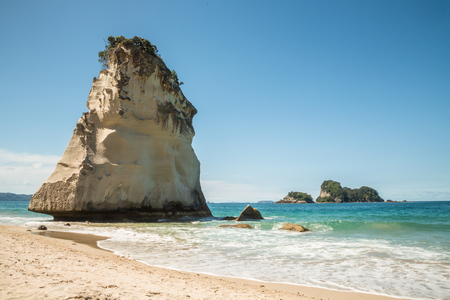 A sea stack off the coast of the Coromandel Penninsula stands above breaking waves on a sandy beach. Above the blue-green waters of the Pacific Ocean stand several small islands in the distance
