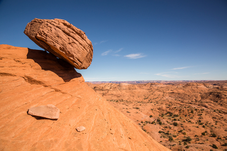 A large sandstone boulder rests precariously over a slope in the desert of the Escalante - Grand Staircase National Monument. The boulder appears to be ready to fall at any moment and slide hundreds of feet into the valley below