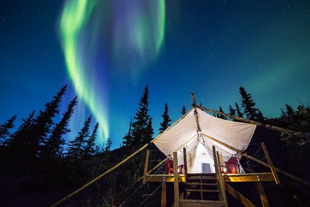 Aurora Borealis lights up the Alaskan night sky over a canvas glamping tent