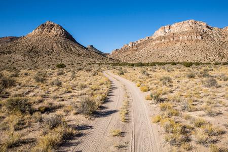 Een pad slingert zich door de lege woestijn van Southwest Utah. Niets dan alsem, grassen en sommige verre jeneverbesbomen op de voorgrond. Boven zijn grote steile kliffen in de rotsachtige heuvels.