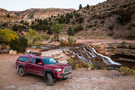 A dirty red truck with camper shell equipped with propane tank, ammo boxes, gas can, and firewood on the roof rack. The truck sits on a rough, rocky trail near a cascading waterfall on the red rock sandstone of the southern Utah desert Stock Photo