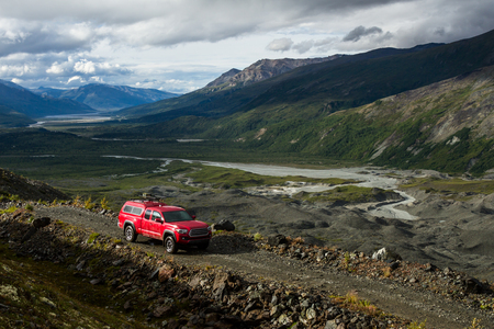 A red truck along a four wheel drive road in the Delta Mountains of the Alaska Range. The road sits high above the Canwell Glacier, covered with moraine on the right side of the image. Stock Photo