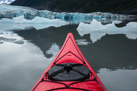 Icebergs float around a red kayak in front of the Spencer Glacier in Alaska. The lake is calm and smooth, barely disturbed by the kayak.