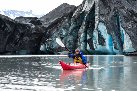 A man paddles his kayak away from the terminus of the Spencer Glacier. The ice is covered with dark moraine - dirt and rock ground up by the glacier. Фото со стока