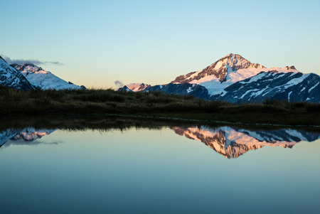 Last light of sunset illuminates the summit of Mount Aspiring, reflected in a puddle above the Cascade Saddle in Mt Aspiring National Park, New Zealand