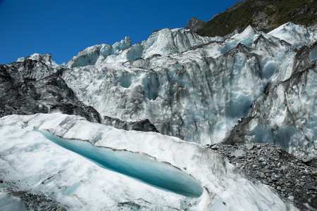 Icefall of Fox Glacier on the South Island of New Zealand. A small crevasse is open toward the camera and tall seracs of ice hang overhead.
