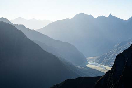 Mountains become mere shadows backlit by the morning sun in Mt Aspiring National Park. Looking from the Cascade Saddle back toward the Raspberry Flat Carpark.