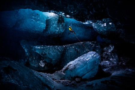 A vertical shaft leads down into a massive ice cave in the SPancer Glacier, Alaska. An ice climber in yellow descends into the cavern under natural light from above.