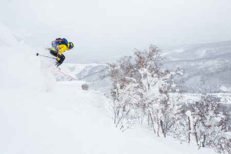 Backcountry skier jumps off a cornice near the summit of a small peak in backcountry Hokkaido, Japan. Yellow jacket, blue backpack powder skiing in Japan. Dropping off a cornice extreme skiing backcountry.