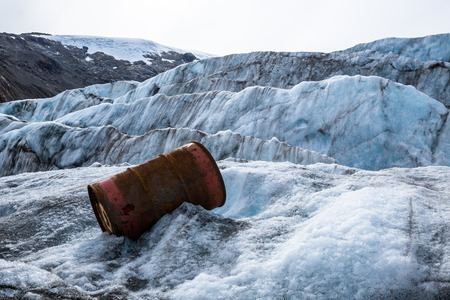 An old oil drum discarded from a mine high in the mountains of British Columbia rusts on top of the Berendon Glacier in the Boundary Range of Canada. 写真素材