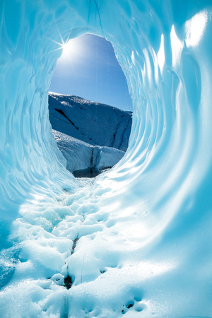 In the Alaskan Backountry on the Matanuska Glacier, the sun shines in through the opening of a massive ice cave. The deep blue ice of the cavern shines in the sun as the light melts the ice and water drips down the walls. Banco de Imagens - 120791454