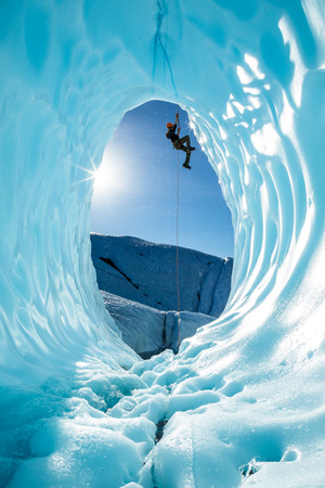 Hanging from a rope fixed above the entrance of a large blue ice cave, an ice climber ascends out of the glacial cavern. The scene is from the Matanuska Glacier, in the wilderness of Alaska.