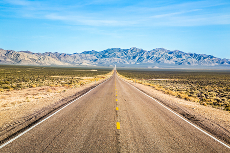Wide open road through Nevada Desert near Area 51. The Extraterrestrial Highway leads to far, distant peaks of desert mountains.