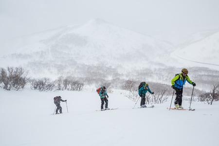 Grupo de cuatro esquiadores de travesía caminando cuesta arriba en Hokkaido. El grupo está esquiando en nieve polvo profunda en el campo cerca de Niseko, Japón, en una tormenta de nieve. Foto de archivo